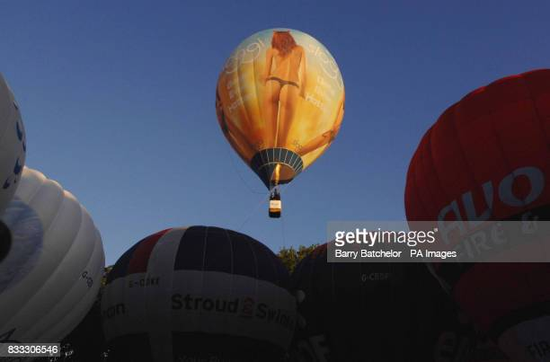 A tethered Sloggi balloon floats above a static display of hot air balloons outside Bristol after flights were cancelled due to the weather