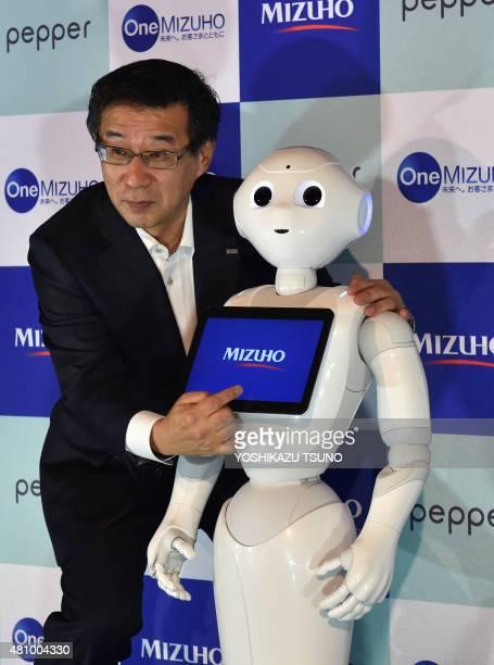 Tetsuhiko Saito a bank executive of Japan's Mizuho Bank presents Japanese telecom giant Softbank's humanoid robot Pepper with a company staff...