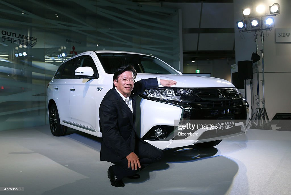 Tetsuro Aikawa president and chief operating officer of Mitsubishi Motors Corp poses next to the company's new Outlander PHEV vehicle during its...