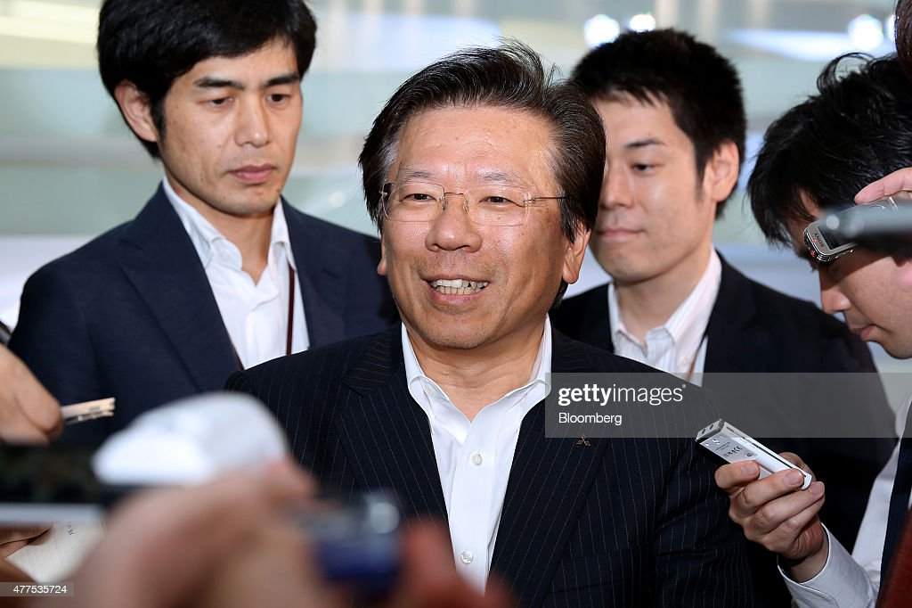 Tetsuro Aikawa president and chief operating officer of Mitsubishi Motors Corp is surrounded by reporters following the unveiling of the company's...