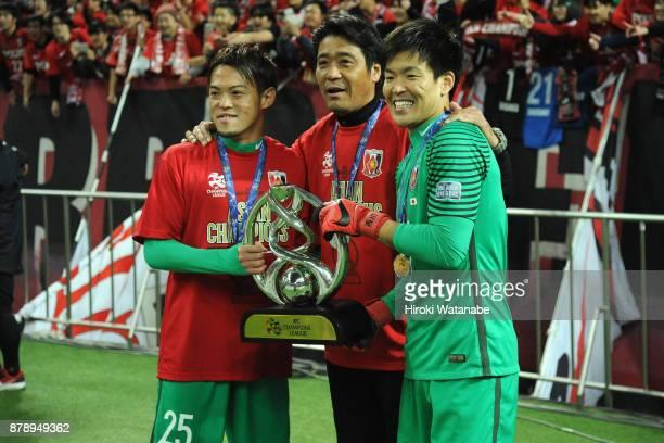 Tetsuya Enomoto goalkeeper coach Hisashi Tsuchida and Shusaku Nishikawa of Urawa Red Diamonds celebrate after the AFC Champions League Final second...