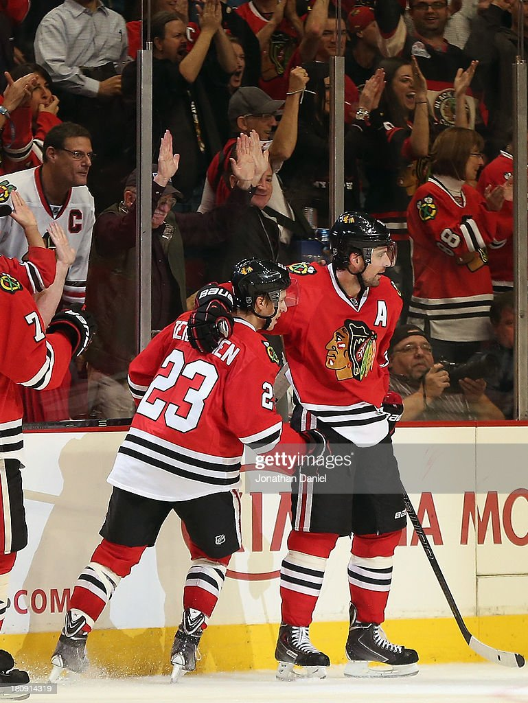 Teuvo Teravainen #23 and Patrick Sharp #10 of the Chicago Blackhawks celebrate Sharp's second period goal against the Detroit Red Wings during an exhibition game at United Center on September 17, 2013 in Chicago, Illinois.