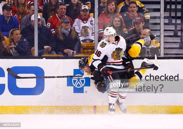 Teuvo Teravainen of the Chicago Blackhawks hits Johnny Boychuk of the Boston Bruins in the first period during the game at TD Garden on March 27 2014...