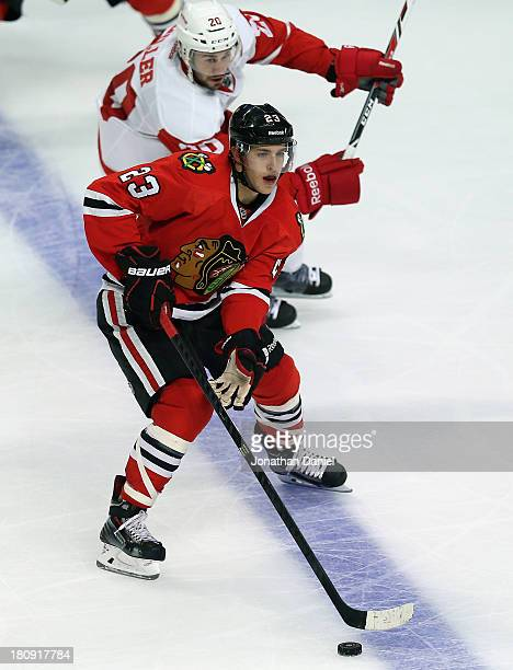 Teuvo Teravainen of the Chicago Blackhawks looks to pass under pressure from Drew Miller of the Detroit Red Wings during an exhibition game at United...