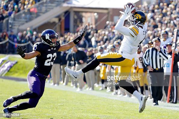 Tevaun Smith of the Iowa Hawkeyes makes a catch while defended by Nick VanHoose of the Northwestern Wildcats during the first quarter at Ryan Field...