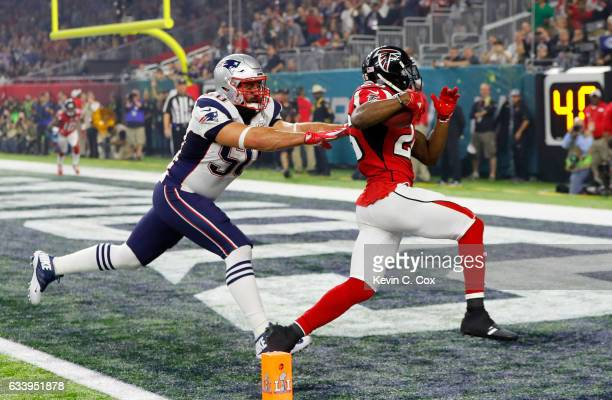 Tevin Coleman of the Atlanta Falcons carries the ball past Rob Ninkovich of the New England Patriots for a six yard touchdown during Super Bowl 51 at...