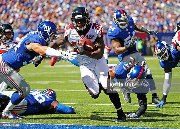 Tevin Coleman of the Atlanta Falcons runs the ball past Mark Herzlich and Uani' Unga of the New York Giants for a first quarter touchdown at MetLife...