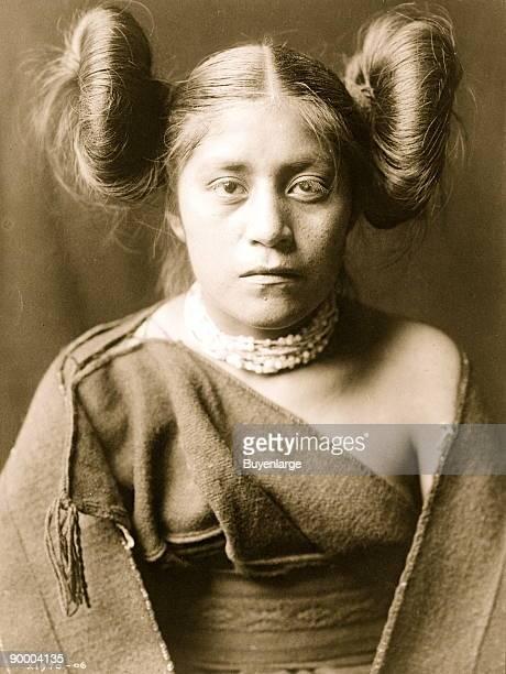 Tewa girl halflength portrait facing front hair arranged in 'squash blossom' fashion