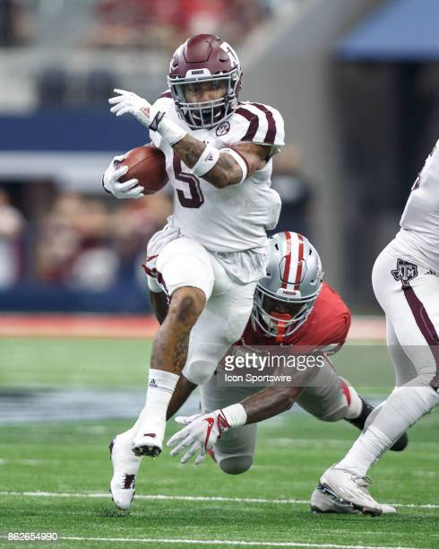 Texas AM Aggies running back Trayveon Williams tries to break away from Arkansas Razorbacks linebacker De'Jon Harris during the college football game...