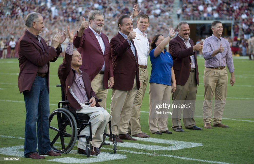 (L-R_ Texas A&M President Michael Yound, Governor Greg Abbott, Texas A&M Regent Charles Schwarts and Texas A&M Chancellor John Sharp acknowledge the crowd at Kyle Field on September 30, 2017 in College Station, Texas.