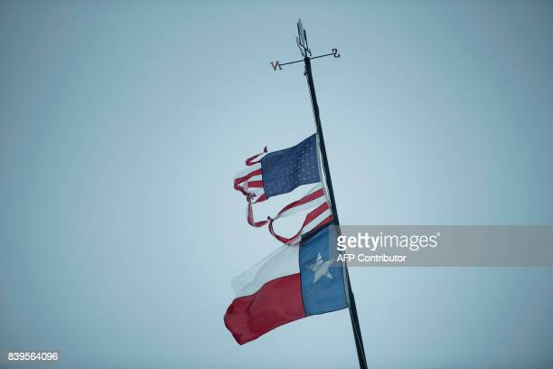 A Texas and US flag are seen as rain from Hurricane Harvey falls on August 26 2017 in Texas City Texas Hurricane Harvey slammed into the Texas coast...