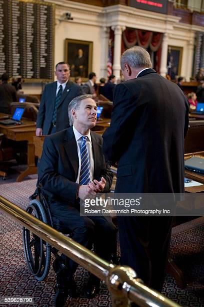 Texas Attorney General Greg Abbott talks with a lawmaker after Governor Rick Perry gave his State of the State speech before a joint session of the...