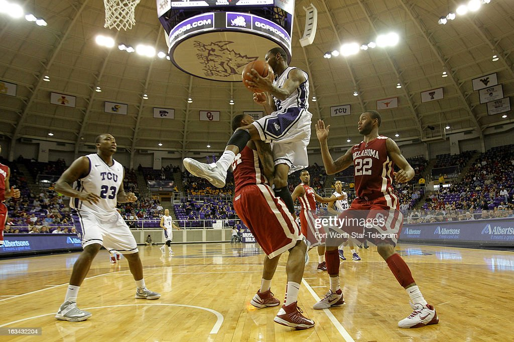Texas Christian's Connell Crossland, top, almost jumps over Oklahoma's Romero Osby as he drives to the basket in the second half at Daniel-Meyer Coliseum in Fort Worth, Texas, on Saturday, March 9, 2013. TCU prevailed, 70-67.