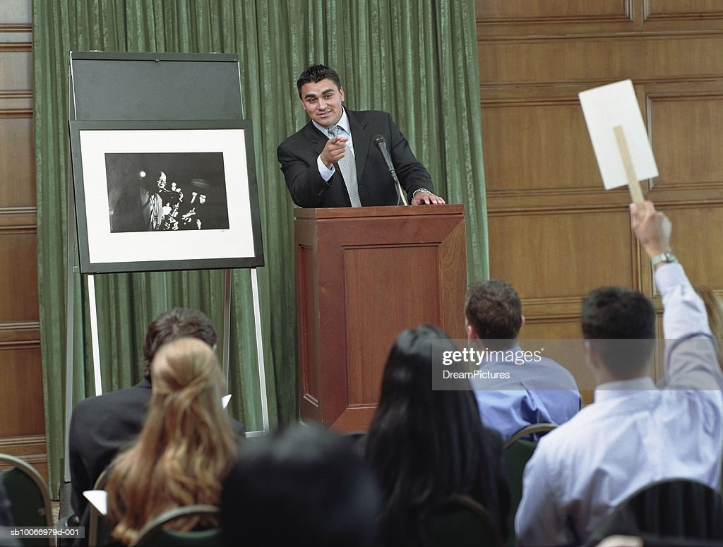 USA, Texas, Dallas, auctioneer taking bid on photograph at auction