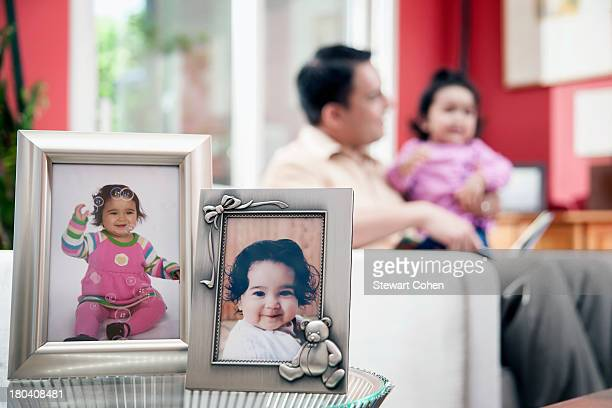 USA, Texas, Dallas, Father and kid (6-11 months) and portraits in frames in foreground