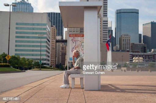 USA, Texas, Dallas, Senior man sitting at bus stop and using mobile phone