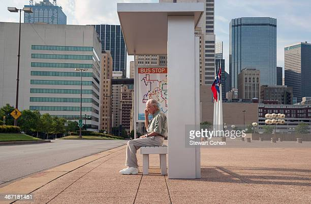 USA, Texas, Dallas, Senior man sitting at bus stop and using mobile phone