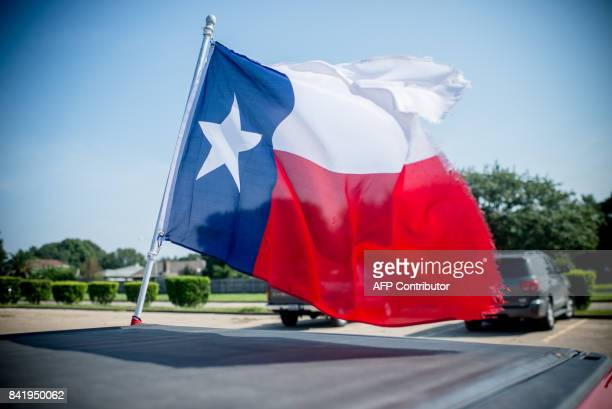 A Texas flag attached to a pickup truck waves outside a shelter in Port Arthur Texas on September 2 2017 As floodwaters receded in Houston nearby...