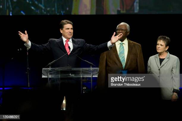 Texas Gov Rick Perry speaks on stage alongside Rev CL Jackson of Houston's Pleasant Grove Missionary Baptist Church and Alice Patterson Texas State...