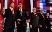 Texas Gov Rick Perry talks with former Massachusetts Gov Mitt Romney while former Speaker of the House Newt Gingrich US Rep Ron Paul and US Rep...