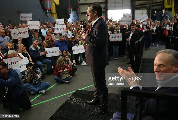 Texas Governor Greg Abbott applauds as Republican presidential candidate US Sen Ted Cruz speaks during a campaign rally where the Texas governor...
