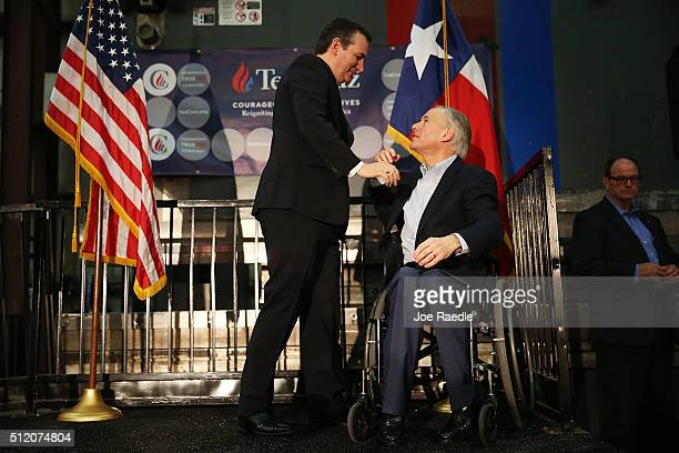 Texas Governor Greg Abbott greets Republican presidential candidate US Sen Ted Cruz during a campaign rally where the Texas governor endorsed him at...
