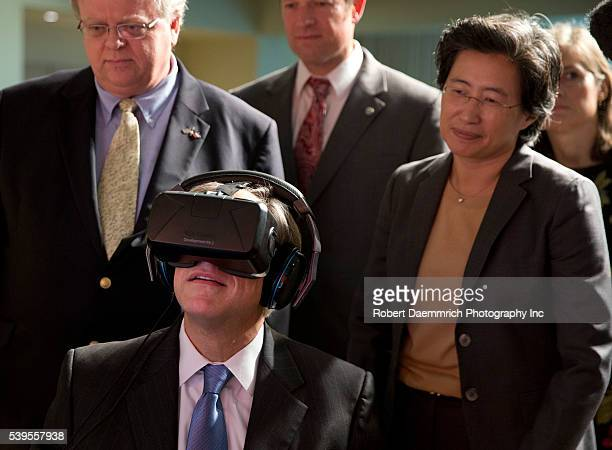 Texas Governor Greg Abbott tests the Oculus virtual reality device at Advanced Micro Devices in Austin as AMD CEO Lisa T Su watches following an...