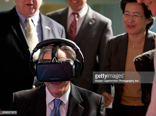 Texas Governor Greg Abbott tests the Oculus virtual reality device at Advanced Micro Devices in Austin as AMD CEO Lisa T Su watches The event...
