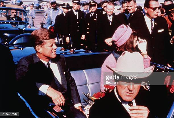 Texas Governor John Connally adjusts his tie as President and Mrs Kennedy in a pink outfit settled in rear seats prepared for motorcade into city...