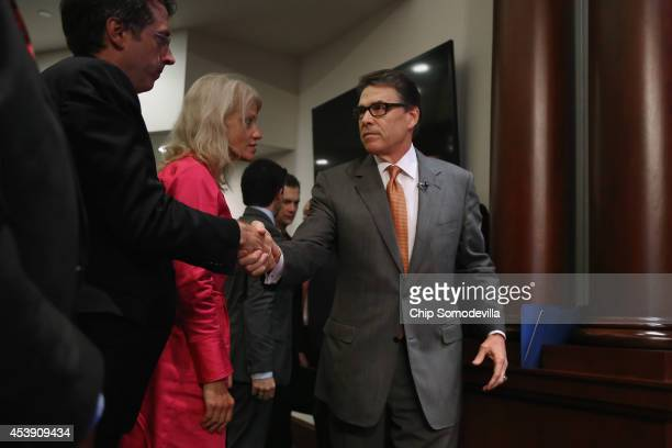 Texas Governor Rick Perry greets National Review Editor Rich Lowry and Republican strategist and pollster Kellyanne Conway before delivering remarks...