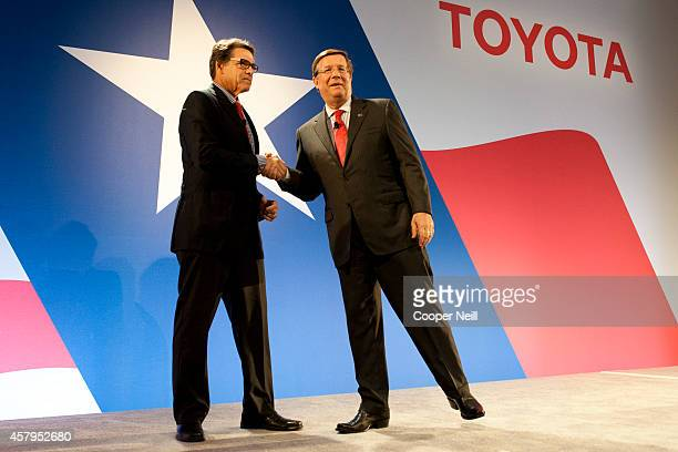 Texas Governor Rick Perry shakes hands with Toyota North America CEO Jim Lentz during the Toyota 'Hello Texas' event on October 27 2014 in Plano Texas