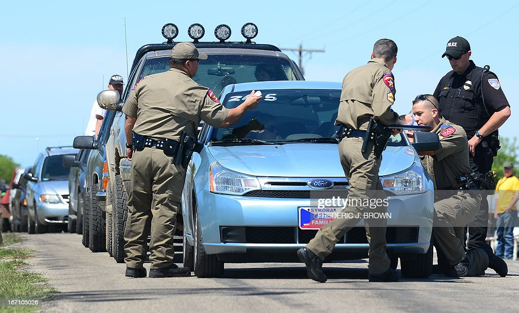 Texas Highway Patrol officers take down details and mark the vehicls of residents being allowed to return to their destroyed homes near the site of the April 17 fertilizer plant blast in West, Texas, on April 20, 2013. Investigators have been treating the blast site as a crime scene, although authorities say the blast was likely caused by a fire at the West Fertilizer Company, and access to the area has been restricted untl today with residents allowed to return. AFP PHOTO/Frederic J. BROWN