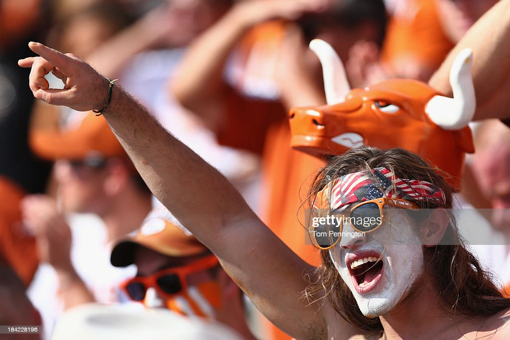 Texas Longhorns fans celebrate after the Longhorns scored against the Oklahoma Sooners in the third quarter at the Cotton Bowl on October 12 2013 in...