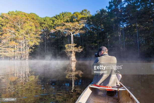USA, Texas, Louisiana, Caddo Lake, bald cypress forest, tourist with camera in kayak