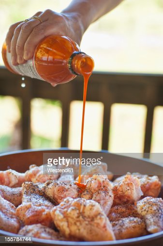 USA, Texas, Mature woman pouring hot buffalo sauce over chicken pieces : Stock Photo