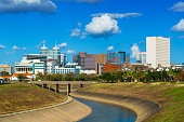 Skyline view of the Texas Medical Center in Houston, with clouds in the background and a canal in the foreground.