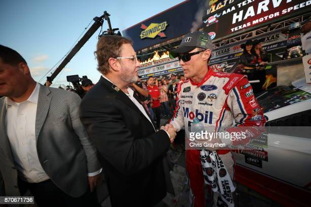 Texas Motor Speedway President Eddie Gossage congratulates Kevin Harvick driver of the Mobil 1 Ford in Victory Lane following the Monster Energy...