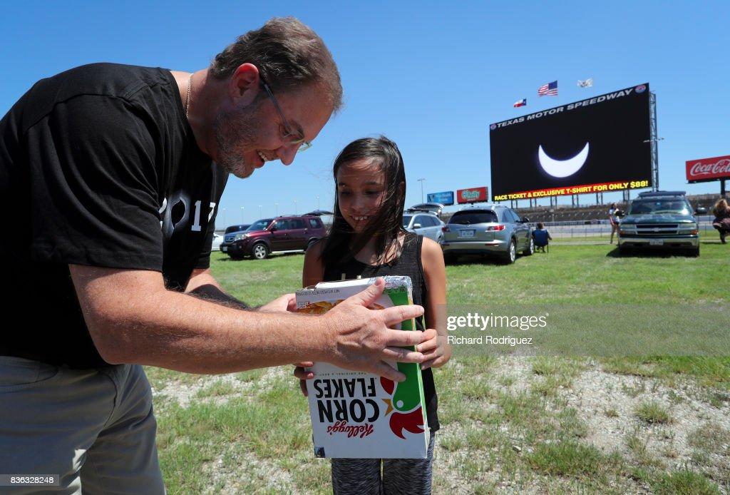 Texas Motor Speedway President Eddie Gossage looks at the solar eclipse through a spectator's homemade viewer as it is broadcast on Big Hoss at Texas Motor Speedway on August 21, 2017 in Fort Worth, Texas. Millions of people have flocked to areas of the U.S. that are in the 'path of totality' in order to experience a total solar eclipse. During the event, the moon will pass in between the sun and the Earth, appearing to block the sun. Fort Worth residents will see about 75 percent of the sun blocked by the moon.