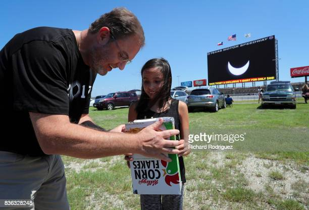 Texas Motor Speedway President Eddie Gossage looks at the solar eclipse through a spectator's homemade viewer as it is broadcast on Big Hoss at Texas...