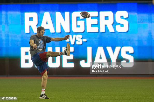 Texas outfielder Jared Hoying punts a football prior to their team's batting practice Texas Rangers work out at Rogers Centre ahead of Sunday's Game...