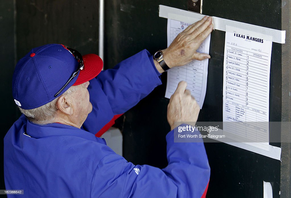 Texas Rangers bench coach Jackie Moore posts the roster on the dugout wall before the spring game against the Kansas City Royals in Surprise, Arizona, Friday, February 22, 2013. The game finished in a 5-5 tie.