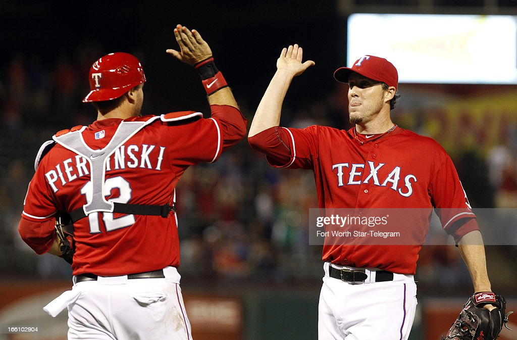 Texas Rangers catcher A.J. Pierzynski (12) goes to high five relief pitcher Joe Nathan (36) who struck out Tampa Bay Rays Ben Zobrist (18) to end the game on Monday, April 8, 2013, in Arlington, Texas. Rangers defeated the Rays, 5-4.