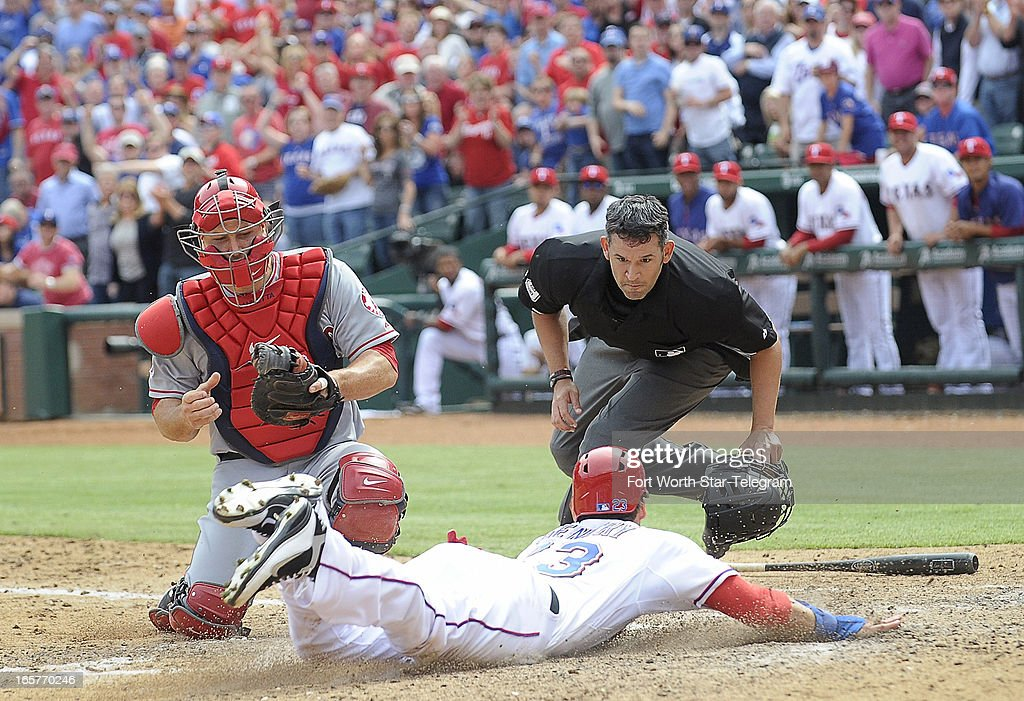 Texas Rangers center fielder Craig Gentry (23) slides safely at home, as Los Angeles Angels catcher Chris Iannetta (17) and umpire Manny Gonzalez (79) watch, in the eighth inning at Rangers Ballpark in Arlington in Arlington, Texas, Friday, April 5, 2013. The Rangers beat the Angels, 3-2.