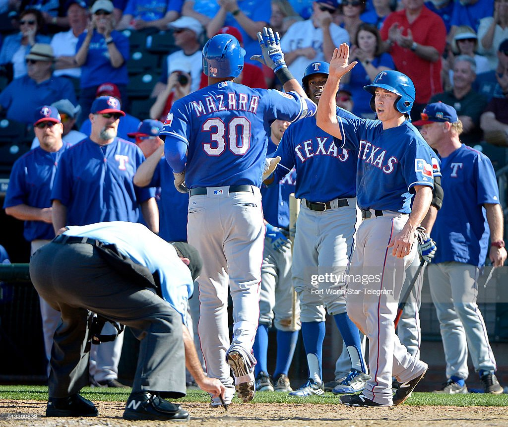 Texas Rangers center fielder James Jones and second baseman Doug Bernier wait for Texas Rangers right fielder Nomar Mazara to cross home plate on his...