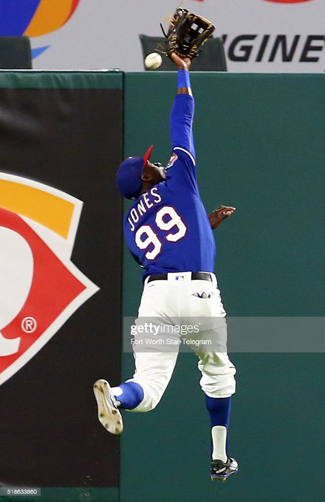 Texas Rangers center fielder James Jones misses a ball hit by the Cleveland Indians' Bryson Myles in the eighth inning during exhibition action at...