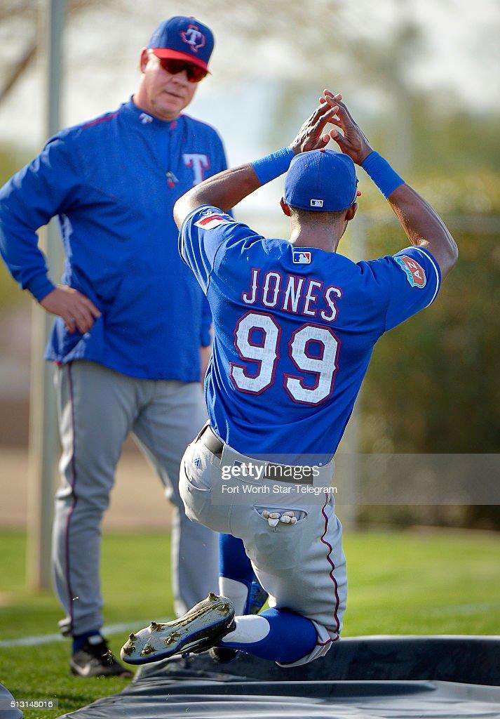 Texas Rangers center fielder James Jones works on his sliding under the eye of bench coach Steve Buechele during the morning workout during Rangers...