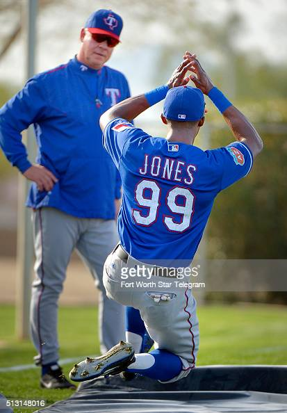 Texas Rangers center fielder James Jones works on his sliding under the eye of bench coach Steve Buechele during the morning workout during Rangers...