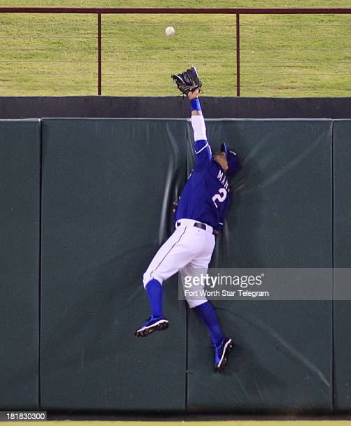 Texas Rangers center fielder Leonys Martin leaps in vain for tworun home run by the Houston Astros' Brandon Laird in the fourth inning at Rangers...