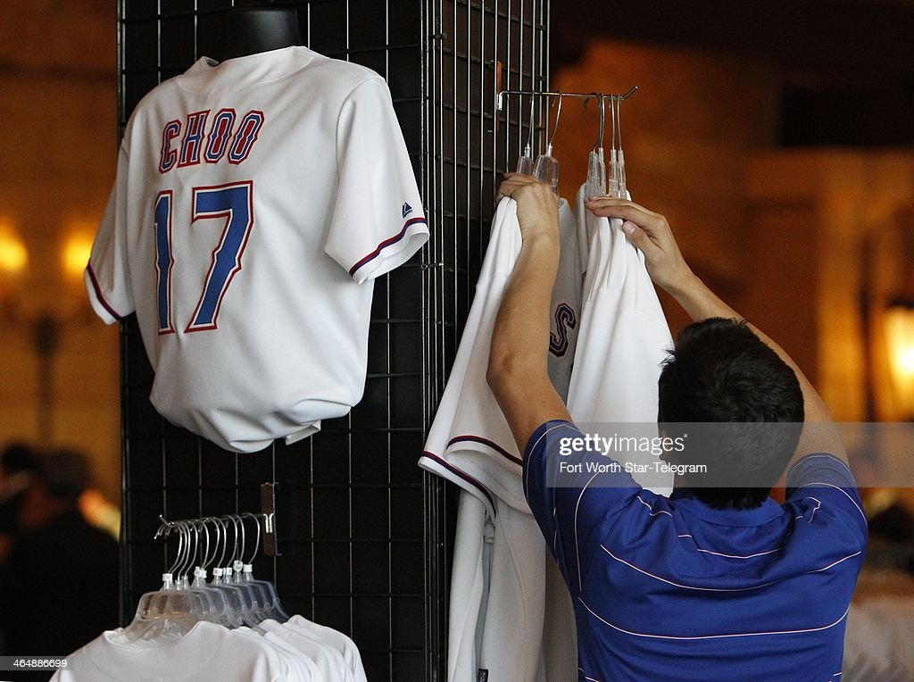 A Texas Rangers employee adjusts jerseys on a rack featuring the name and number of Shin-Soo Choo at an event prior to the Rangers Awards Banquet at the Gaylord Texan in Grapevine, Texas, Friday, Jan. 24, 2014.