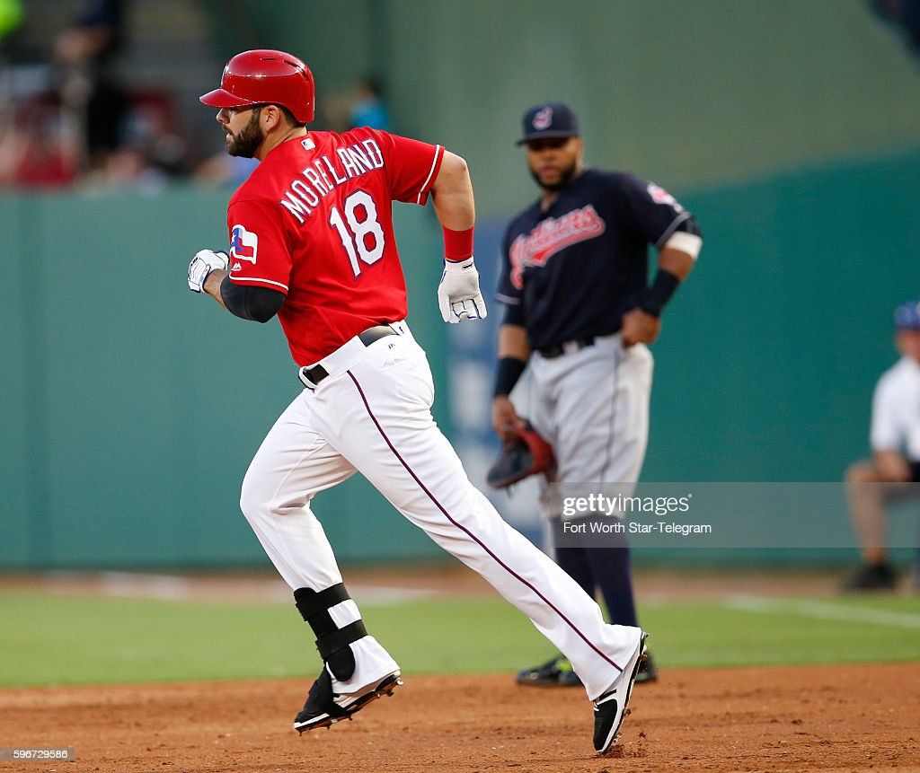 Texas Rangers first baseman Mitch Moreland circles the bases on his grand slam home run in front of Cleveland Indians designated hitter Carlos...